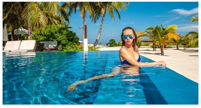 woman-at-beach-pool-in-maldives-ABXDYVM
